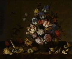 A vase of flowers with shells on a ledge
