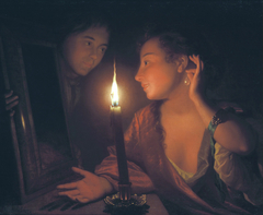 Young woman admiring an ear-pendant by candlelight