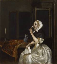 Young woman with a glass of wine, holding a letter in her hand