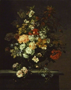 Still life of mixed flowers and a vase on a ledge