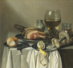 Still life with ham, lemon, a roll, a glass of wine, and others on a table