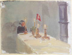 Birthday. A woman at the end of a table with candles and a flag