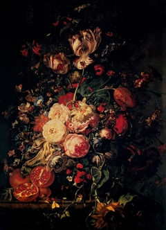 Flowers in a glass vase, with pomegranites, on a marble balustrade