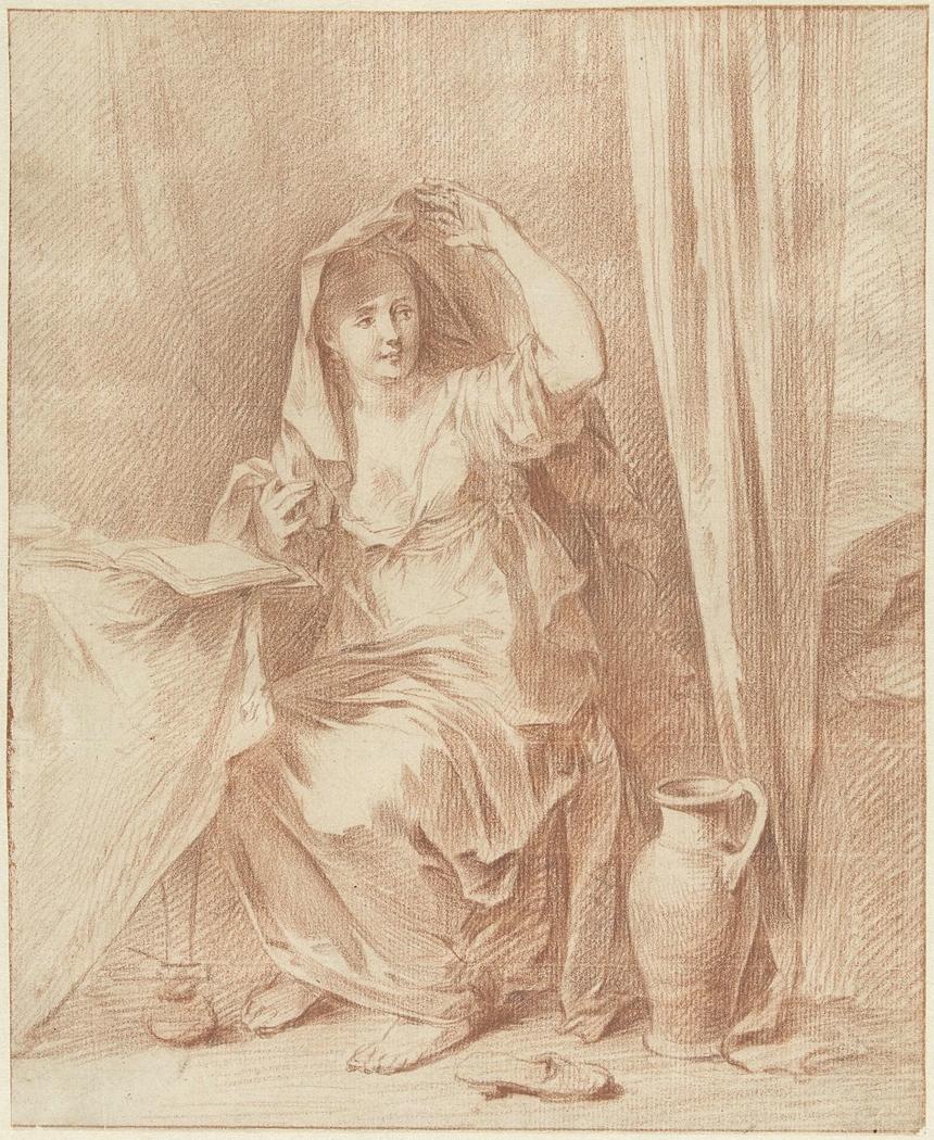 Vrouw zittend aan een tafel achter een boek