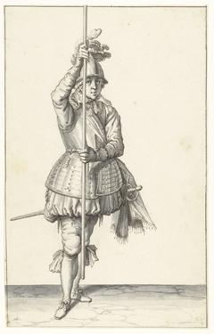 Soldaat, van voren gezien, die zijn spies met beide handen rechtop voor zich iets boven de grond vasthoudt